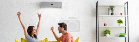 Photo for Panoramic shot of excited man and woman sitting under air conditioner at home - Royalty Free Image