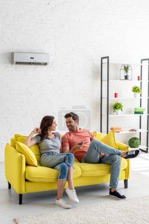 Photo for Young man and woman talking while sitting on yellow sofa under air conditioner at home - Royalty Free Image