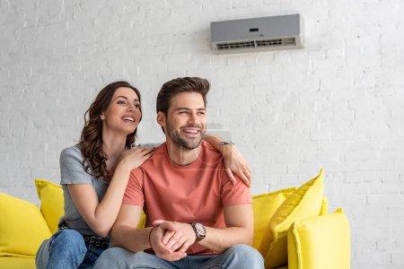 Photo pour Couples heureux s'asseyant sur le sofa jaune sous le climatiseur à la maison - image libre de droit