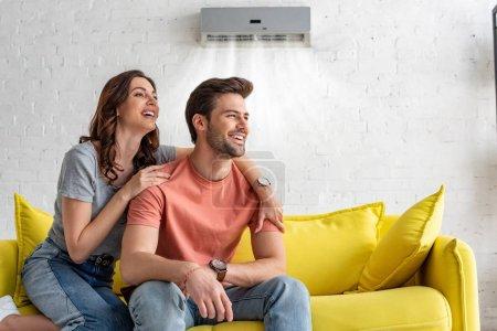 Photo pour Couples joyeux s'asseyant sur le sofa jaune sous le climatiseur à la maison - image libre de droit