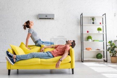 Photo pour Un jeune homme et une jeune femme se reposant sur un canapé jaune sous la climatisation à la maison - image libre de droit