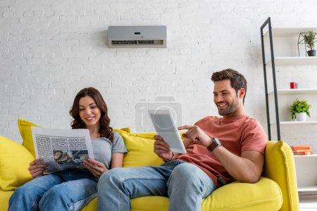 Photo pour Jolie femme lisant le journal et l'homme beau utilisant la tablette numérique tout en s'asseyant sur le sofa jaune sous le climatiseur à la maison - image libre de droit