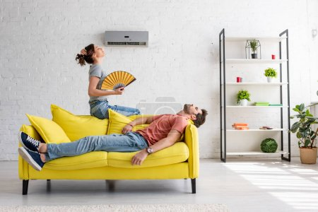 Photo for Exhausted man lying on yellow sofa under air conditioner near woman with hand fan - Royalty Free Image