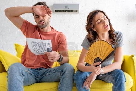 Photo pour Homme et femme épuisés s'asseyant sur le sofa et souffrant de la chaleur à la maison - image libre de droit