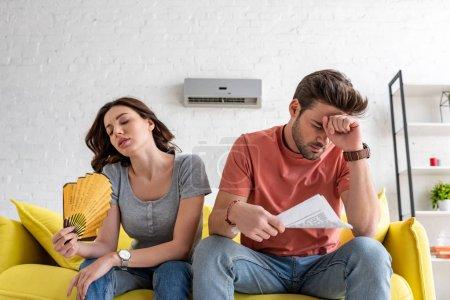 Photo pour Homme avec le journal et la femme avec le ventilateur de main s'asseyant sur le sofa et souffrant de la chaleur à la maison - image libre de droit