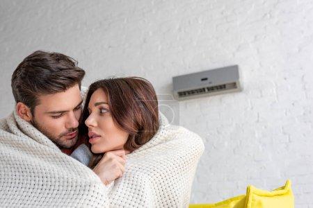 Photo pour Couple congelé se réchauffer sous la couverture et en regardant les uns les autres tout en étant assis sous le climatiseur à la maison - image libre de droit