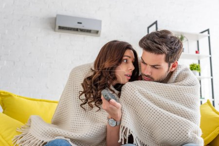Photo pour Couple congelé se réchauffer sous la couverture tout en s'asseyant sur le sofa sous le climatiseur à la maison - image libre de droit