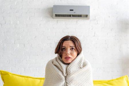 Photo pour Gelé jeune femme réchauffement sous couverture tandis que assis sur canapé sous climatiseur à la maison - image libre de droit