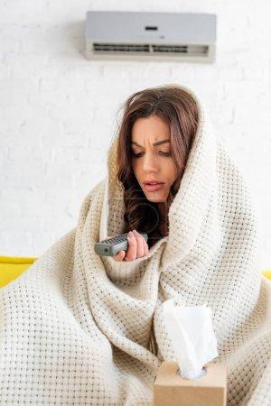Photo pour Femme congelée avec le réchauffement de télécommande sous la couverture tout en s'asseyant sous le climatiseur à la maison - image libre de droit