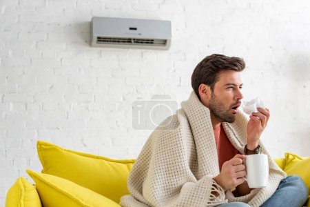 Foto de Sick man with cup and paper napkin warming under blanket while sitting under air conditioner at home - Imagen libre de derechos