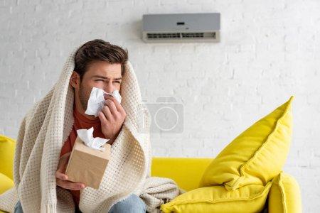 Photo pour Homme malade avec des serviettes de papier se réchauffant sous la couverture tout en s'asseyant sous le climatiseur à la maison - image libre de droit