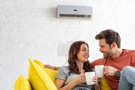 Photo pour Couples heureux avec des tasses s'asseyant sur le sofa sous le conditionneur d'air à la maison - image libre de droit
