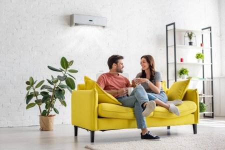 Photo for Happy young couple talking and holding cups while sitting on yellow sofa under air conditioner at home - Royalty Free Image