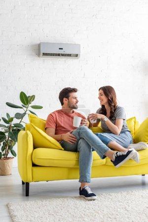Photo pour Bel homme avec jolie petite amie tenant des tasses tout en étant assis sur le canapé sous climatiseur à la maison - image libre de droit