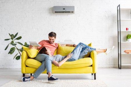 Foto de Hombre feliz con novia sonriente relajarse en el sofá amarillo bajo aire acondicionado en casa - Imagen libre de derechos