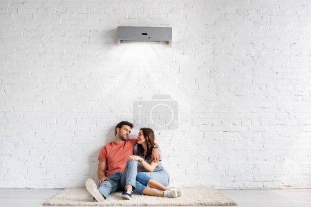 Photo pour Jeunes couples heureux étreignant tout en s'asseyant sur le plancher près du mur blanc sous le climatiseur - image libre de droit