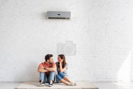 Photo for Smiling couple talking while sitting on floor under air conditioner at home - Royalty Free Image
