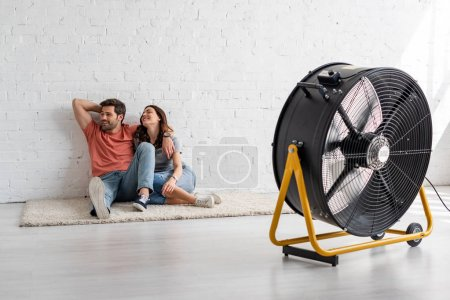 Photo for Young smiling couple sitting on floor by white wall in front of blowing electric fan - Royalty Free Image