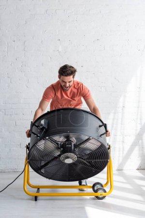 Photo pour Homme beau excité restant près du mur blanc devant le ventilateur électrique soufflant - image libre de droit