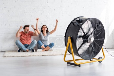 Photo for Excited man and woman sitting on floor by white wall in front of blowing electric fan - Royalty Free Image