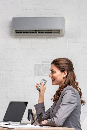Photo pour Femme d'affaires de sourire retenant la télécommande tout en s'asseyant sous le climatiseur au lieu de travail - image libre de droit