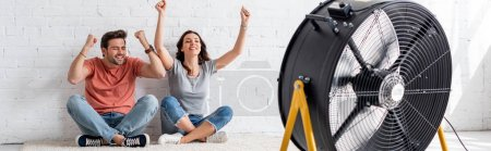 Photo for Panoramic shot of excited man and woman sitting on floor with raised hands in front of blowing electric fan - Royalty Free Image