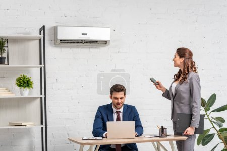 Foto de Young businesswoman holding remote control while standing near man using laptop at workplace - Imagen libre de derechos