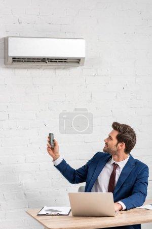 Photo pour Homme d'affaires beau retenant la télécommande tout en s'asseyant au lieu de travail sous le climatiseur - image libre de droit
