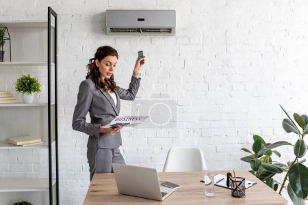 Photo for Beautiful businesswoman reading business newspaper while standing under air conditioner with remote control - Royalty Free Image