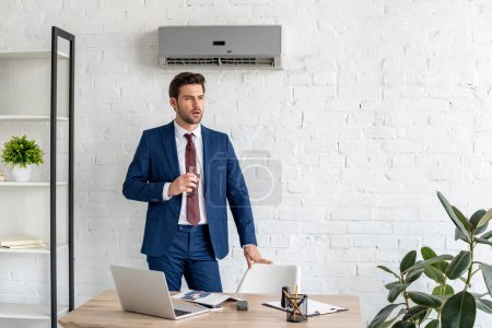 schöner Geschäftsmann mit einem Glas Wasser, während er in der Nähe seines Arbeitsplatzes unter einer Klimaanlage steht