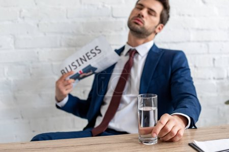Photo for Selective focus of handsome businessman waving business newspaper while sitting at workplace with closed eyes - Royalty Free Image