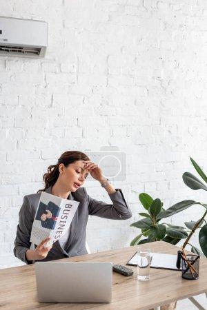 Photo pour Femme d'affaires épuisée agitant le journal d'affaires tout en s'asseyant au lieu de travail et souffrant de la chaleur - image libre de droit