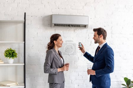 Foto de Smiling businesspeople talking while standing under air conditioner in office - Imagen libre de derechos