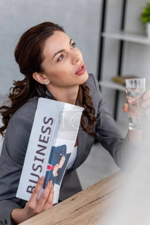 Photo for Selective focus of beautiful businesswoman holding glass of water and waving business newspaper while suffering from heat in office - Royalty Free Image