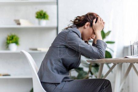 Photo pour Femme d'affaires épuisée retenant des mains près de la tête tout en souffrant du chef dans le bureau - image libre de droit