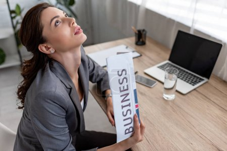 pretty businesswoman waving business newspaper and looking up while sitting at workplace in office