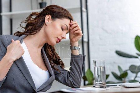Photo pour Jolie femme d'affaires avec les yeux fermés souffrant de la chaleur dans le bureau - image libre de droit