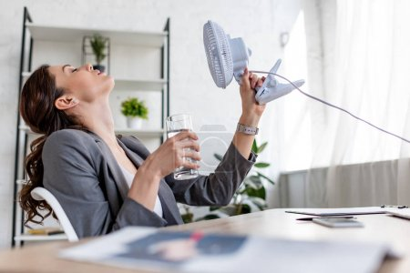 Photo for Selective focus of attractive businesswoman holding blowing electric fan and glass of water while suffering from heat in office - Royalty Free Image