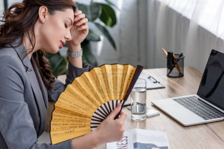 Photo pour Young businesswoman waving hand fan while sitting at workplace and suffering from heat in office - image libre de droit
