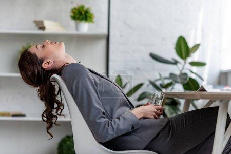 Photo pour Femme d'affaires épuisée s'asseyant sur la présidence avec les yeux fermés et retenant le verre de l'eau tout en souffrant de la chaleur dans le bureau - image libre de droit