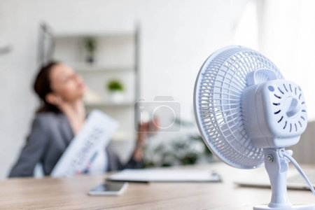 Photo for Selective focus of businesswoman suffering from heat while sitting near electric fan - Royalty Free Image