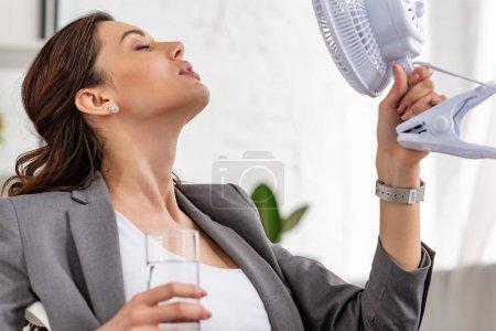 Photo pour Belle femme d'affaires retenant ventilateur électrique et verre d'eau avec les yeux fermés tout en souffrant de la chaleur dans le bureau - image libre de droit