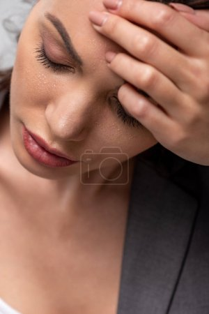 Photo for Attractive woman suffering from heat and holding head on forehead with closed eyes on grey - Royalty Free Image