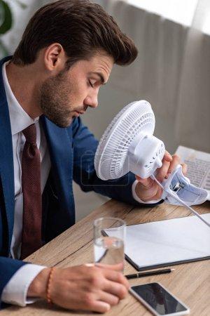 Photo pour Homme d'affaires épuisé s'asseyant devant le ventilateur électrique soufflant tout en souffrant de la chaleur dans le bureau - image libre de droit
