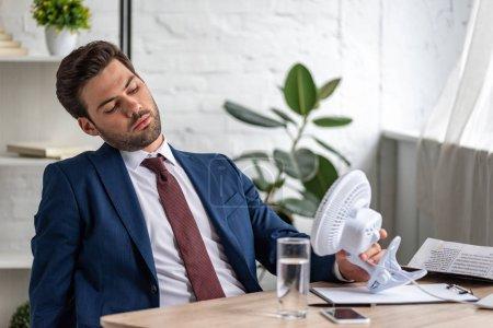 Photo pour Beau homme d'affaires épuisé souffrant de chaleur tout en s'asseyant au lieu de travail devant le ventilateur électrique soufflant - image libre de droit