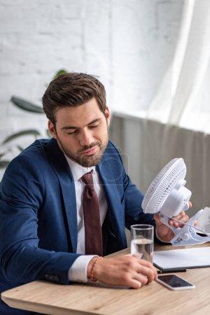 Photo pour Homme d'affaires épuisé retenant le ventilateur électrique tout en s'asseyant au lieu de travail et souffrant de la chaleur - image libre de droit