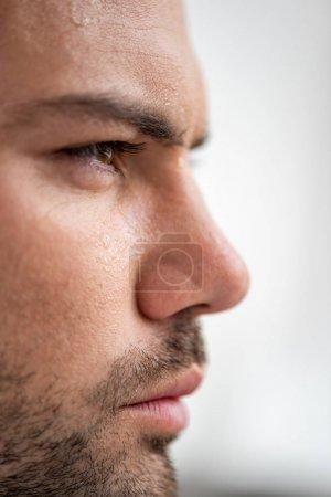 Photo pour Verticale de bel homme avec le visage moissé souffrant de la chaleur sur le fond blanc - image libre de droit