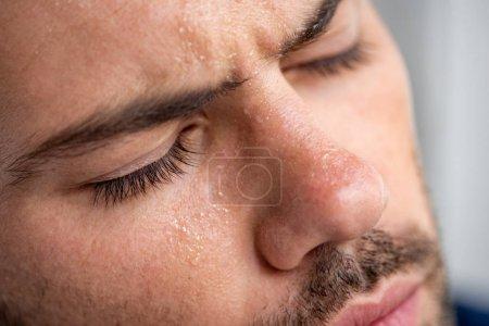 Photo pour Fermez-vous vers le haut de l'homme avec le visage moissé souffrant de la chaleur avec les yeux fermés sur le gris - image libre de droit