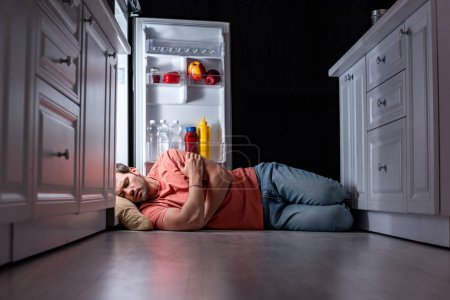 Photo for Exhausted young man sleeping on kitchen floor near open refrigerator - Royalty Free Image