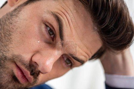 Photo pour Verticale de l'homme beau épuisé avec le visage moite souffrant de la chaleur sur le blanc - image libre de droit